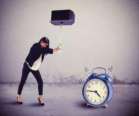 woman with clock: Woman breaks with a hammer an alarm
