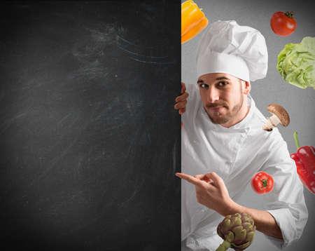 칠판 및 야채 배경 가진 웃는 요리사
