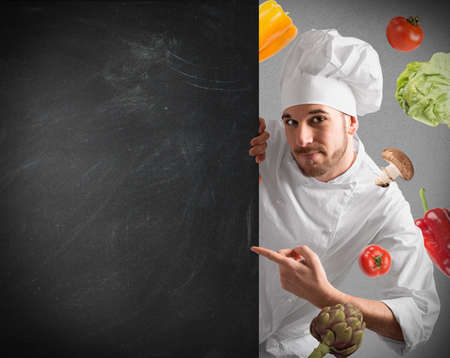 Smiling chef with blackboard and vegetables background