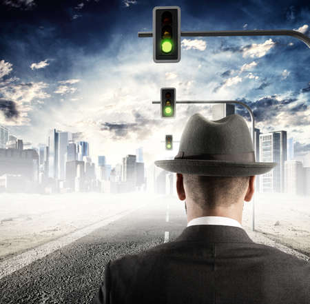 Man walking on street with traffic lights Stock Photo