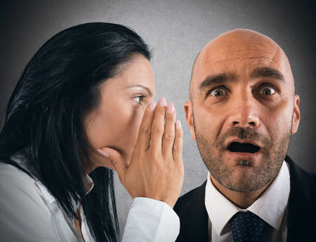 chismes: Mujer que habla en secreto a un hombre Foto de archivo