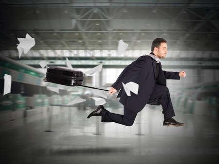 voyage avion: L'homme de passagers fonctionne avec une valise à l'aéroport