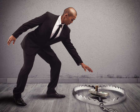 savings problems: Businessman takes some money into a trap