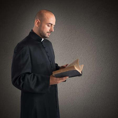 religion catolica: Hombre sacerdote lee el texto sagrado biblia