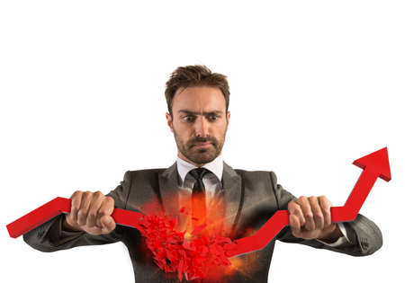 Angry businessman breaks a big red arrow Stock Photo