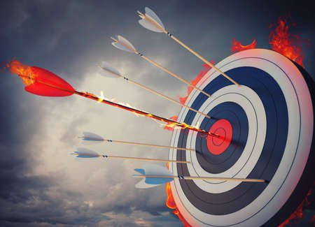 focus on: Flaming arrow hitting the center of target Stock Photo
