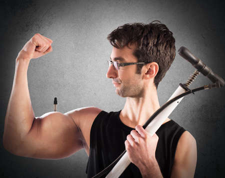 hombre flaco: Boy hinchado músculos del brazo con una bomba Foto de archivo