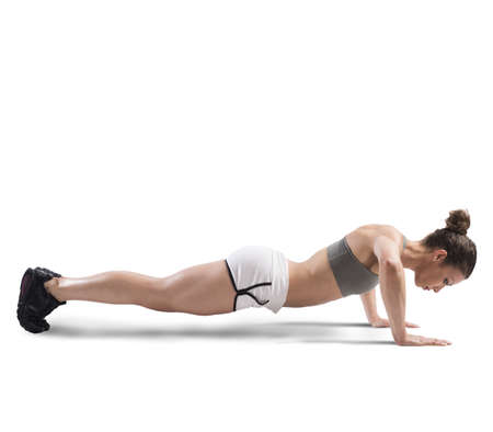 forceful: Athletic girl is training doing push up Stock Photo