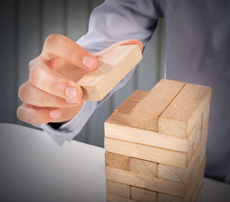Man puts the last wood block of puzzle Stock Photo