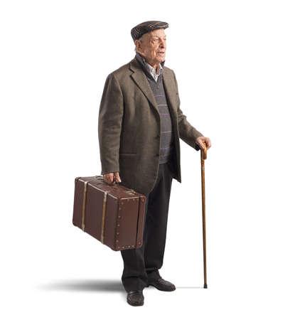 老人はスーツケースと棒で歩く