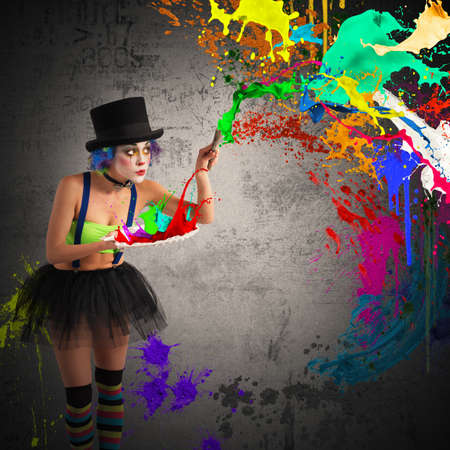 Painter clown paints with brush and palette Stock Photo