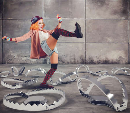 traps: Clown walks with skills between big traps Stock Photo