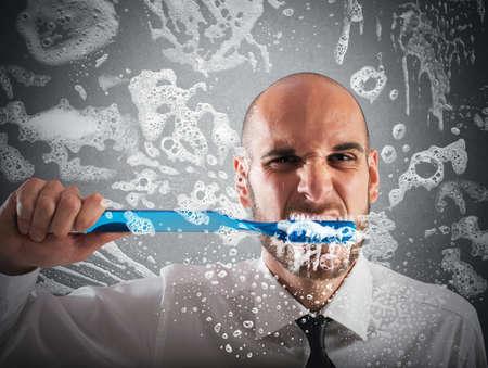 大きな歯ブラシで歯を磨く男