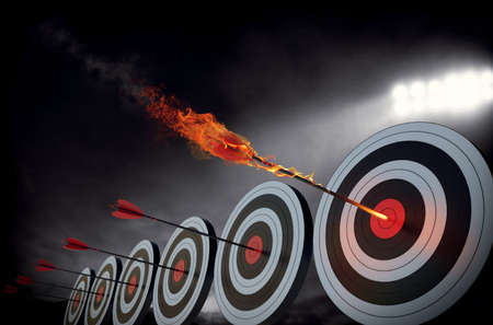 Flaming arrow hitting the center of target Фото со стока