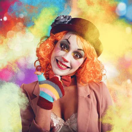 Vrolijke en lachende clown tussen multi-color poeders