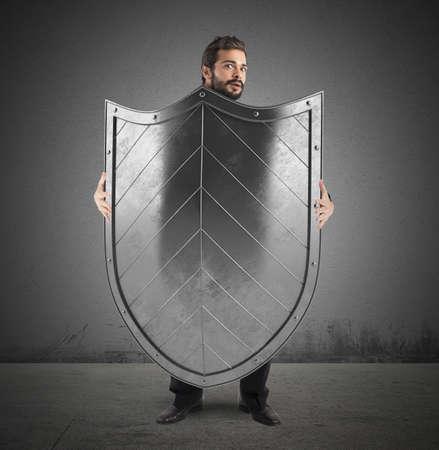 Frightened man hiding behind a big shield