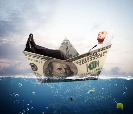 million fish: Businessman relaxed on a boat of banknote Stock Photo