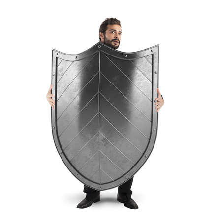Frightened man hiding behind a big shield