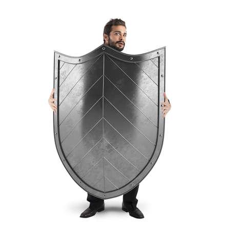 man behind: Frightened man hiding behind a big shield