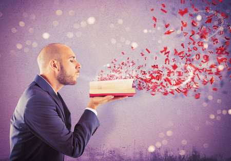 book pages: Man blows on book and fly letters Stock Photo