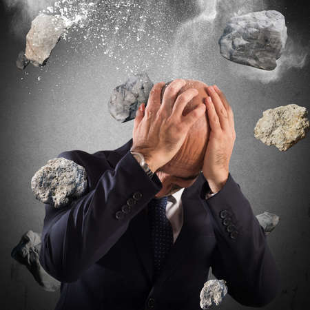 financial protection: Man protects himself from a boulders rain