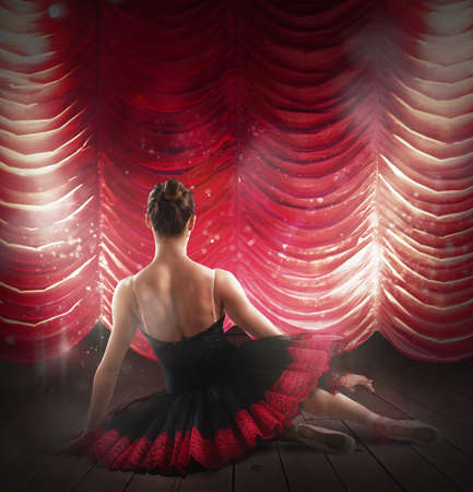 enact: Dancer posing behind the red velvet curtains