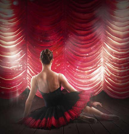 Dancer posing behind the red velvet curtains