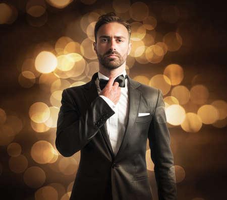 Homem elegante com papillon no fundo dourado Imagens