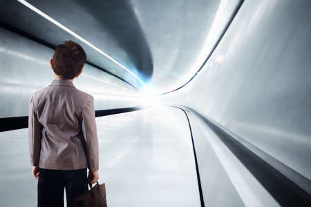 rapid steel: Kid with luggage walks in futuristic tunnel