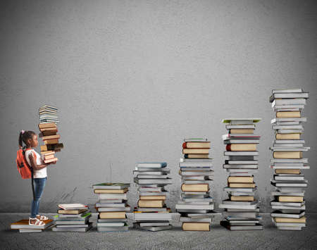 Child with backpack climbs a books scale Stock Photo