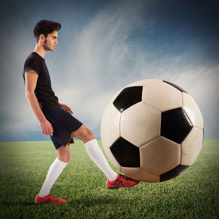 big: Teenage soccer player plays with big soccerball Stock Photo