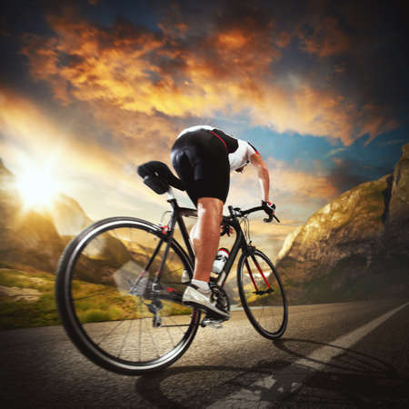 road bike: Cyclist rides on the road between mountains
