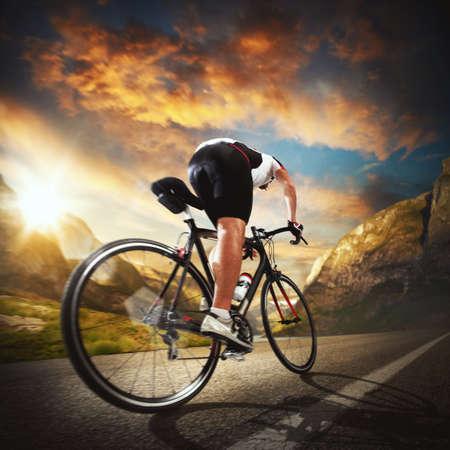 Radfahrer fährt auf der Straße zwischen Bergen Lizenzfreie Bilder