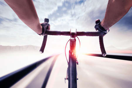 faster: Cyclist pedaling faster with bicycle on road