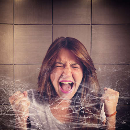Girl screaming trapped in a spider web Stock Photo