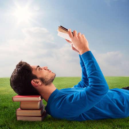 personas leyendo: El muchacho se relaja con un libro en el césped