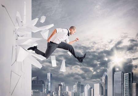 Man running fast breaks through a wall 写真素材