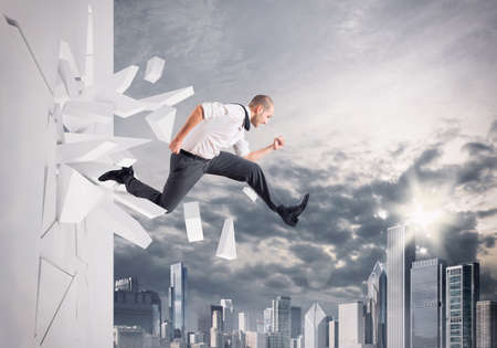 difficult mission: Man running fast breaks through a wall Stock Photo