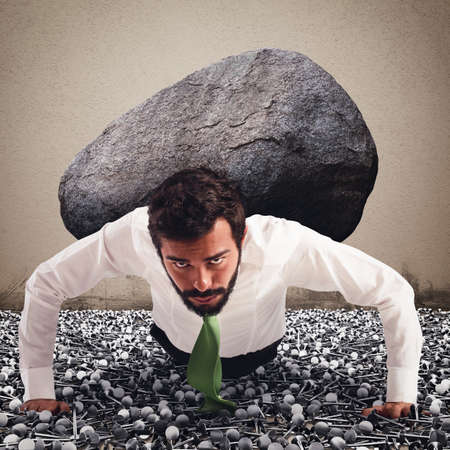 Businessman holds on back a big boulder
