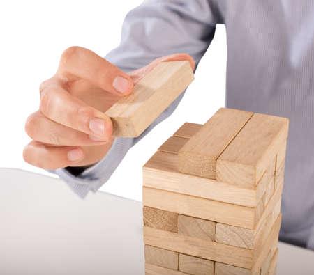wood block: Man puts the last wood block of puzzle Stock Photo