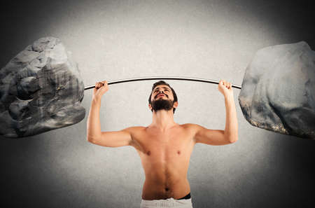 clumsiness: Goofy guy lifting a barbell with boulders Stock Photo