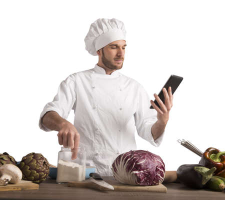 preparing food: Chef reads a recipe from the tablet