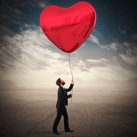 sentiment: Man holds a big red heart balloon Stock Photo