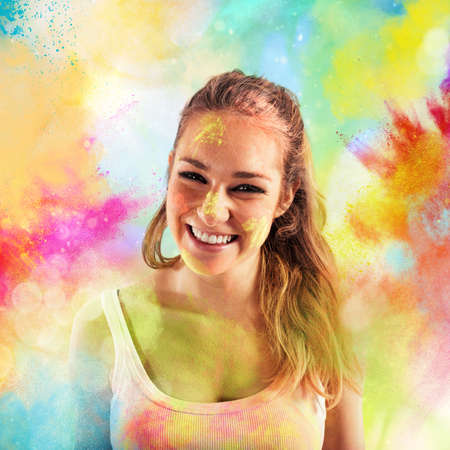 Laughing girl on background of colored powders