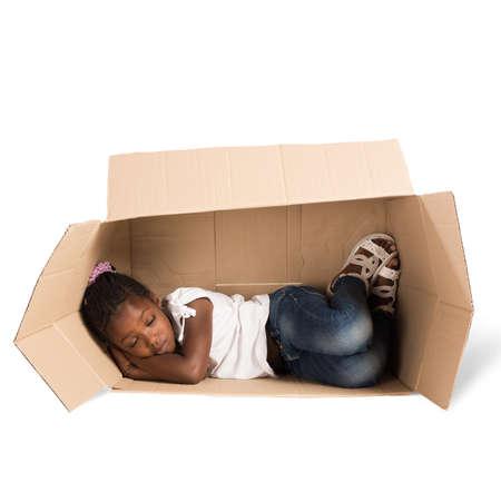 pobre: Pobre niña duerme en un cartón Foto de archivo