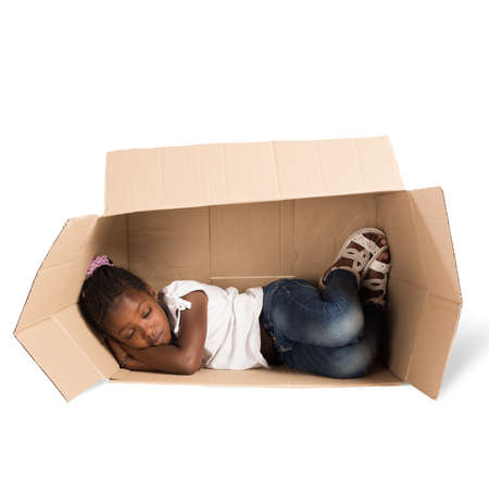 hopelessness: Poor little girl sleeps in a cardboard Stock Photo