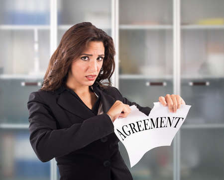 financial official: Angry businesswoman tears a sheet document agreement