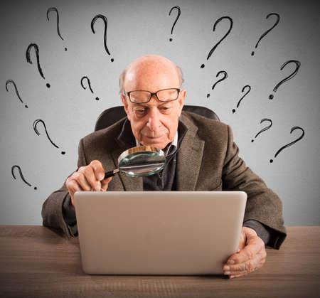 anciano confundido mira a la computadora Foto de archivo