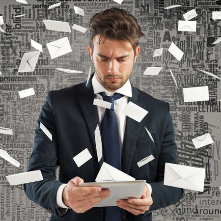 Businessman with tablet and many letters envelopes