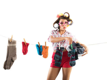 clothes peg: Vintage housewife with curlers stretches the laundry
